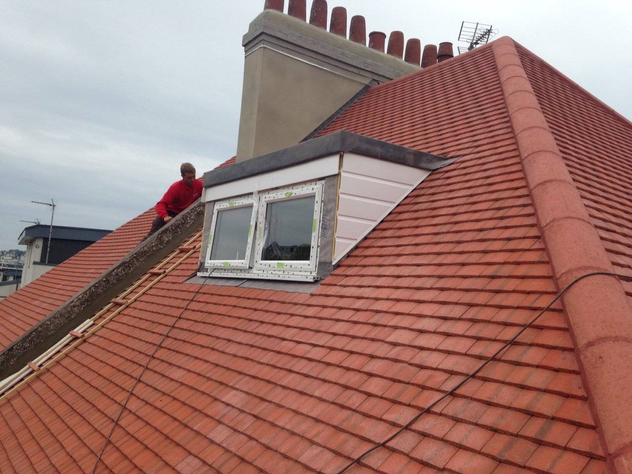 roofer re tiling a house and fitting dorma windows