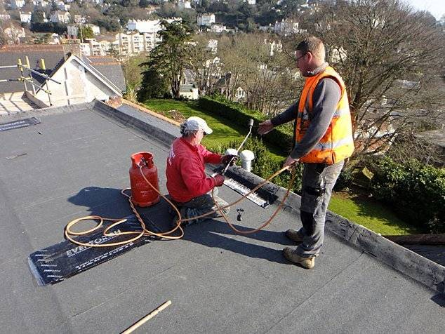 roofer repairing a flat roof with heat treatment