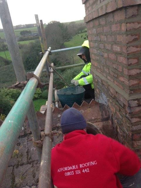 roofers performing repairs on a brick chimney