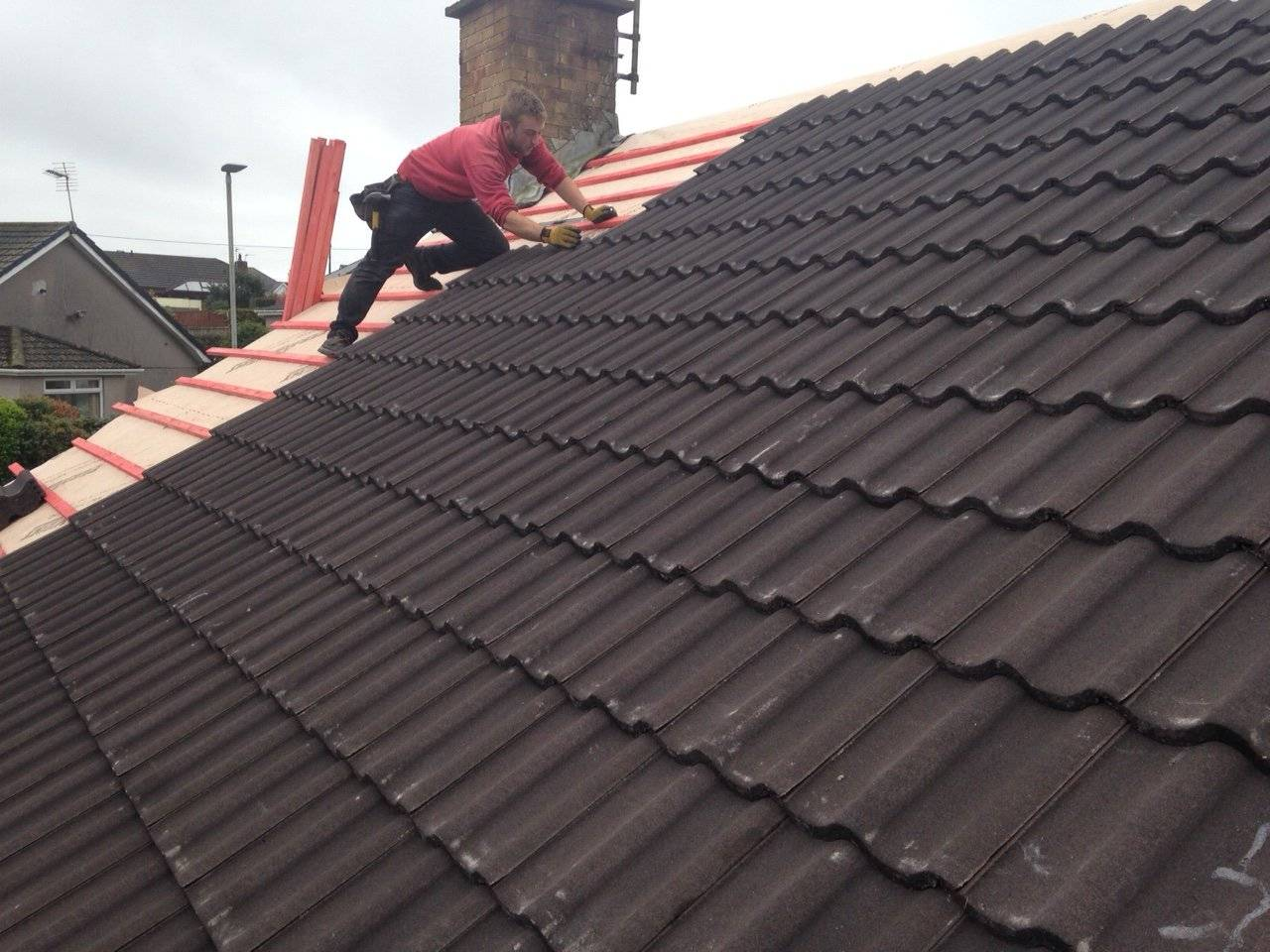new tiled pitched roof being finished by roofer