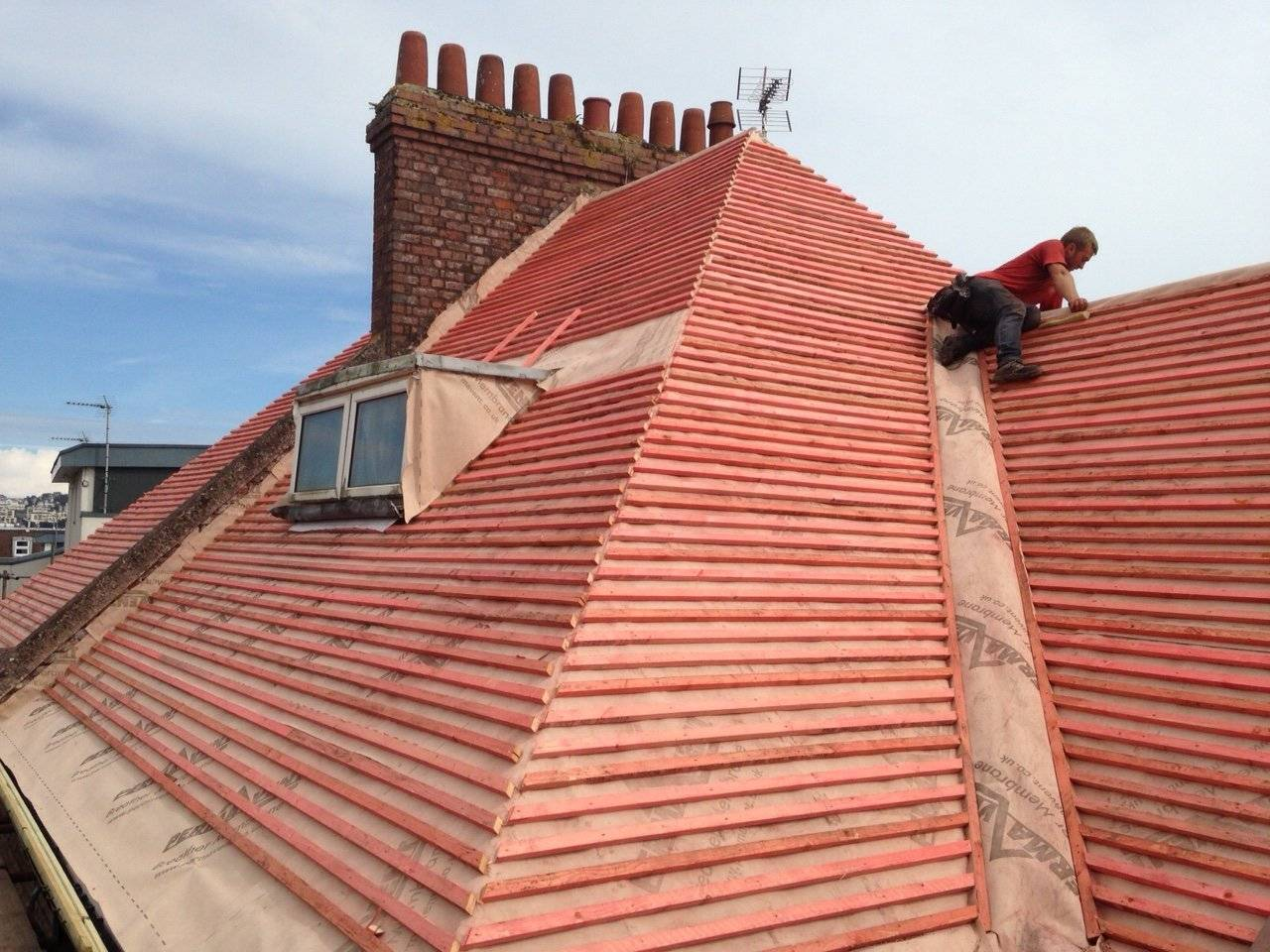 roofer retiling a roof with clay roof tiles