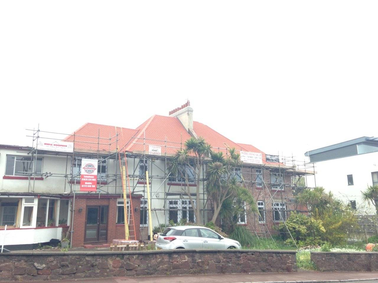 house having a new roof with scaffolding around the building