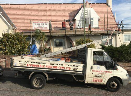 affordable roofing van and team working on roof slating and roof repair